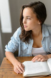 Thoughtful teenage girl book looking away home Royalty Free Stock Photo