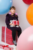 Thoughtful teenage girl with gifts Stock Photos