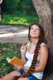 Thoughtful teenage girl with notebook Stock Images
