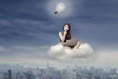 Thoughtful teenage girl sitting on cloud Stock Photography