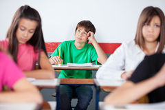 Thoughtful Teenage Male Student Sitting At Desk. Thoughtful teenage male student looking up while sitting at desk in classroom Royalty Free Stock Photography