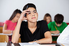 Thoughtful Teenage Schoolboy Sitting At Desk Royalty Free Stock Photos