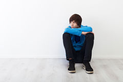 Thoughtful teenager. The times when every thought is big - serious teenager boy sitting Stock Image