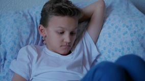 Thoughtful teenager boy lying in bed, touching tablet screen