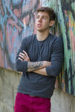 Thoughtful teenager in casual clothes. Portrait of thoughtful teenager in casual clothes with arm tattooed in city Royalty Free Stock Photography