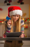 Thoughtful teenager girl in santa hat with credit Stock Photos
