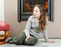 Thoughtful teenager girl sitting near fireplace. Blond thoughtful teenager girl sitting on carpet near fireplace Royalty Free Stock Photo