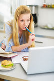 Thoughtful teenager girl studying in kitchen Royalty Free Stock Image