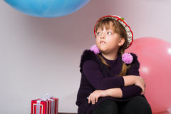 Thoughtful teenager in a hat sitting with a gift Stock Image