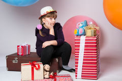 Thoughtful teenager in a hat sitting on a suitcase Royalty Free Stock Images