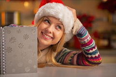 Thoughtful teenager in santa hat with notepad Stock Photos