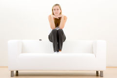 Thoughtful teenager on sofa. Thoughtful teenager sat on back of white sofa, studio background Stock Photo
