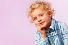 Thoughtful thinking blond curly hair boy portrait Stock Photos
