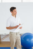 Thoughtful trainer with clipboard in gym at hospital. Thoughtful male trainer with clipboard in the gym at hospital Stock Image