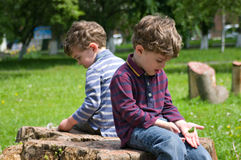 Thoughtful twins. Identical twins sit back to back on the stump of the tree with pensive mood Stock Photo