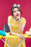 Thoughtful unhappy pinup girl ironing clothes Royalty Free Stock Photos