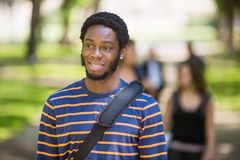 Thoughtful University Student At Campus. Thoughtful male university student at campus with friends in background Royalty Free Stock Images