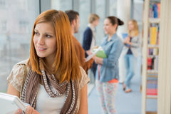 Thoughtful university student in library. Thoughtful university student with classmates in background at library Stock Photography