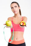 Thoughtful unsure fitness girl holding apple, measuring tape and cake Stock Image