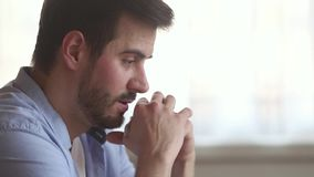 Thoughtful upset millennial man concerned about problem making difficult decision stock footage