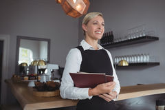 Thoughtful waitress standing with menu card Stock Photo