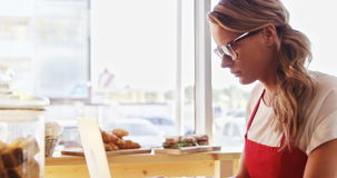 Thoughtful waitress using laptop. In cafe 4k stock footage