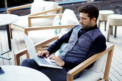 Thoughtful wealthy businessman work on-line on net-book while sits at modern restaurant terrace Stock Images