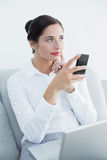 Thoughtful well dressed woman with cellphone and laptop on sofa Stock Photo
