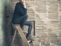 Thoughtful womamn sitting on stepladder Stock Image