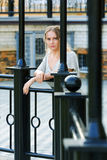 Thoughtful woman against a railing. Royalty Free Stock Photos
