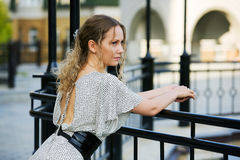 Thoughtful woman against a railing. Royalty Free Stock Photography