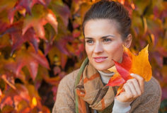 Thoughtful woman with autumn leafs Stock Photo