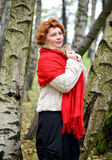 The thoughtful woman of average years in a red stole costs among. Birches in the wood Stock Photo
