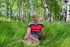 The thoughtful woman of average years sits on a grass in the bir Stock Photo