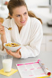 Thoughtful woman in bathrobe eating breakfast Royalty Free Stock Photos