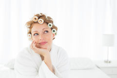 Thoughtful woman in bathrobe and hair curlers sitting on bed Royalty Free Stock Photo