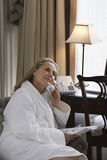 Thoughtful Woman In Bathrobe Using Phone In Living Room Royalty Free Stock Images