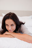 Thoughtful woman on the bed. Thoughtful young woman on the bed Royalty Free Stock Photos