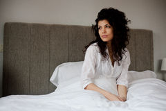 Thoughtful woman in bed. Inside bedroom looking away Stock Photography