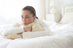 Thoughtful Woman In Bed. Thoughtful young woman looking away while lying in bed Stock Photos