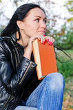 Thoughtful woman with a book Stock Image