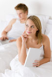 Thoughtful woman with book in bed. Man in background Royalty Free Stock Photography