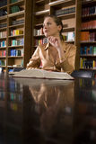 Thoughtful Woman With Book At Desk In Library Royalty Free Stock Image