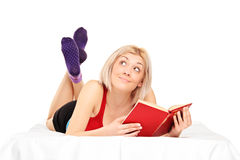 Thoughtful woman with a book lying on her bed. Beautiful thoughtful woman with a book lying on her bed isolated on white background Stock Photos