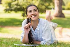 Thoughtful woman with book and pen relaxing in park Stock Photos