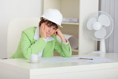 Thoughtful woman - builder in helmet. The thoughtful woman - a builder in a helmet royalty free stock photo