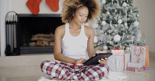 Thoughtful woman catching up on Christmas news Stock Images