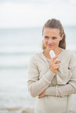 Thoughtful woman with cell phone standing on beach Royalty Free Stock Photos