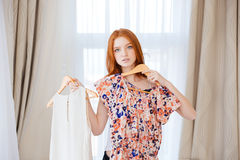 Thoughtful woman choosing clothes to put on Stock Photography