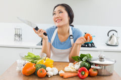 Thoughtful woman chopping vegetables in kitchen. Thoughtful smiling young woman chopping vegetables in the kitchen at home Stock Image